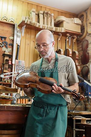 geigenbauer prueft fertiges instrument zu seiner