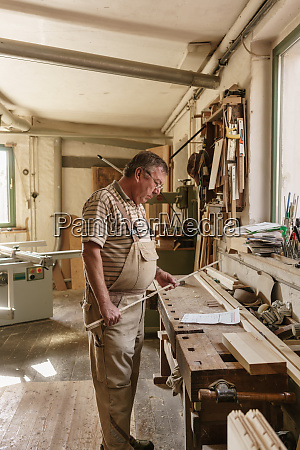 craftsman in his wood workshop holding