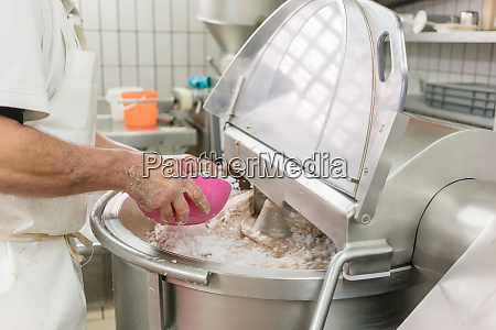 metzger erdet fleisch in schleifmaschine um