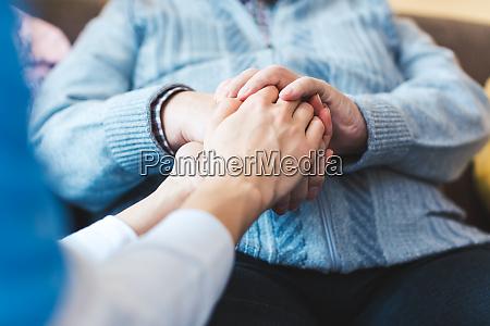 krankenschwester haelt hand eines aelteren mannes