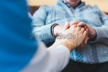 nurse holding hand of a senior