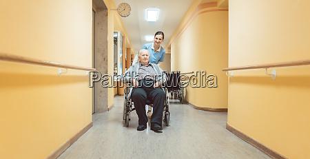 krankenschwester hilft einem aelteren mann im