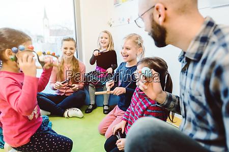 vorschullehrer und kinder musizieren gemeinsam
