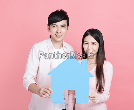 young couple hands holding paper house