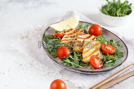 frischer salat mit gegrilltem aluminiumkaese kirschtomaten