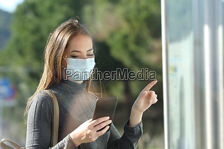 pendler mit schutzmaske ueberpruefen busfahrplan