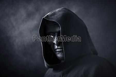 gruselige figur in kapuzenmantel mit maske