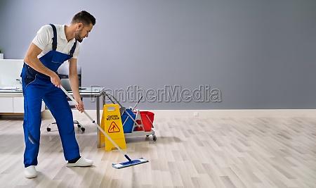 arbeiter mopping boden mit nassen boden