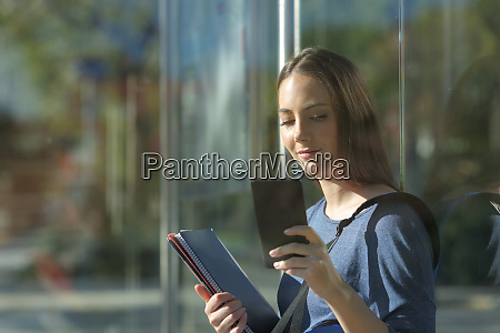 student checking smart phone at the
