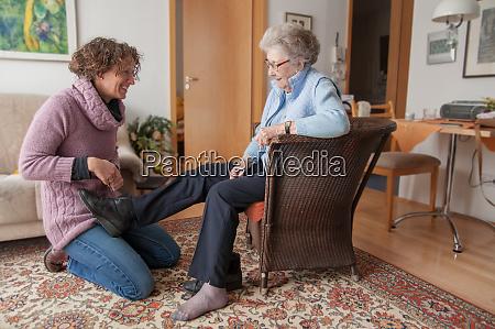 betreuerin hilft senior beim anziehen ihrer