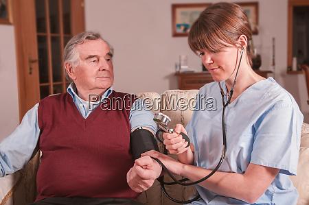 junge krankenschwester kuemmert sich um senior