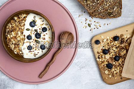 schuessel muesli und heidelbeeren auf joghurt