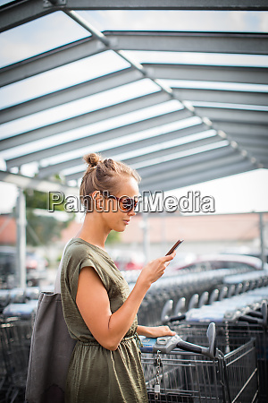 pretty young woman going grocery shopping
