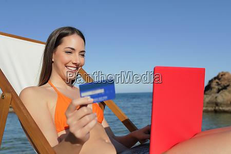 glueckliche touristin online auf ihrem laptop