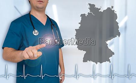 deutschlandkarte arzt zeigt auf betrachter konzept