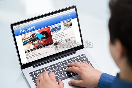 geschaeftsmann liest nachrichten auf dem laptop