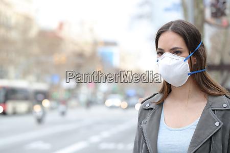 frau traegt schutzmaske mit blick auf