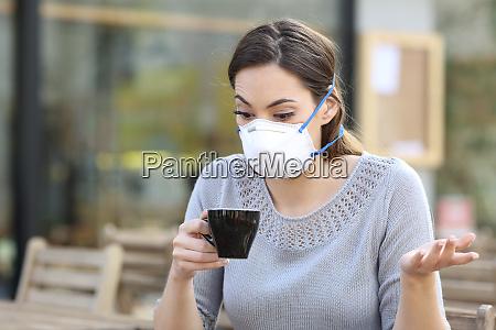 verwirrtes maedchen haelt eine tasse kaffee