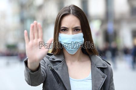 ernstes maedchen tun stoppschild mit maske