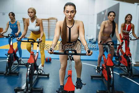 frauen auf stationaeren fahrraedern im fitnessstudio