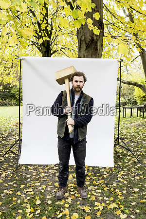 portrait of bearded man holding wooden