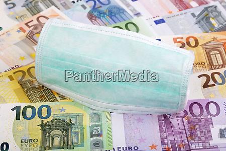 schutzmaske auf europaeischem geldhintergrund