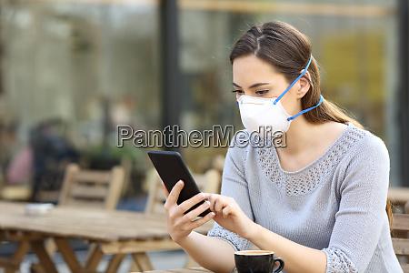 frau mit schutzmaske schaut auf telefon
