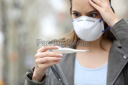 besorgte maedchen mit maske ueberpruefen thermometer