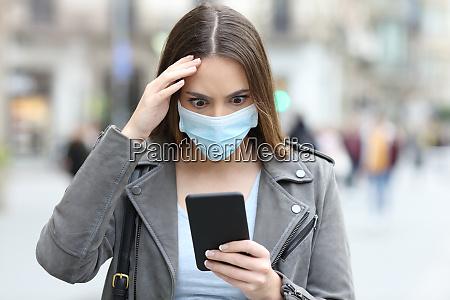 besorgte frau mit maske ueberpruefen telefon