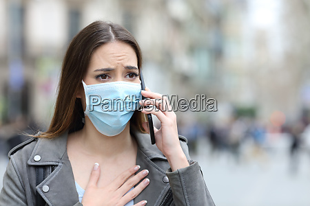 scared girl with mask calling on