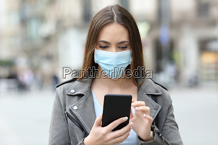 serious girl with mask checking her