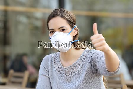 frau die daumen hoch traegt schutzmaske