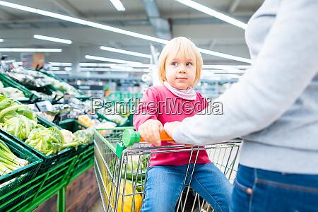mutter und kleinkind mit einkaufswagen im
