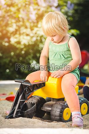 kind reitet auf einem spielzeugtraktor auf