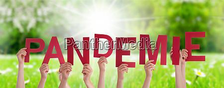 menschen haende halten wort pandemie bedeutet
