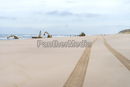 excavators work on the beach