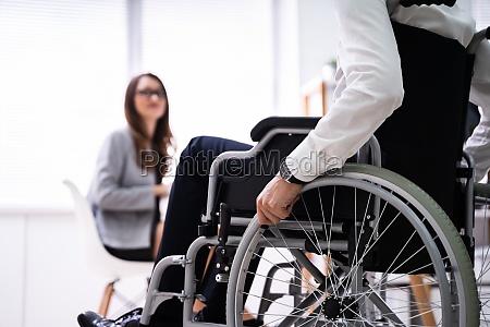 behinderte geschaeftsfrau sitzt im rollstuhl
