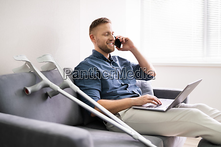 man with leg injury using laptop