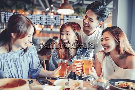 glueckliche junge gruppe essen und bier