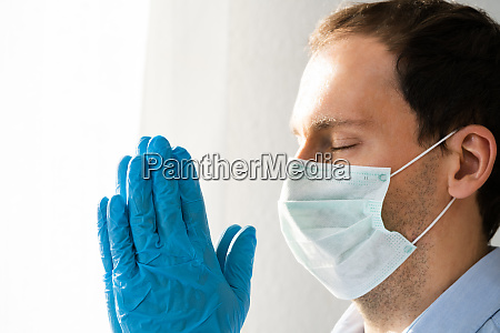 mann betet waehrend coronavirus pandemie