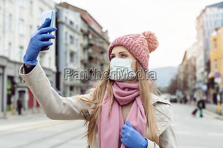 frau mit medizinischer maske und handschuhen