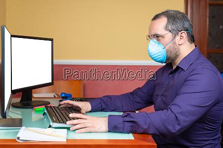 mann mit medizinischer maske arbeiten im