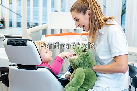 kleines kind in zahnarztpraxis lernen wie