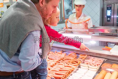 familie kauft frisches fleisch im supermarkt