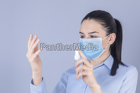 girl with protective mask holding alcohol