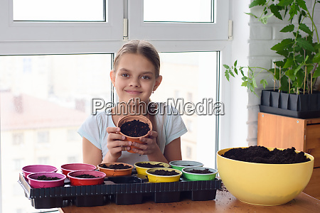 cheerful girl holding a pot of