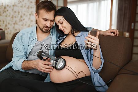 ehemann und schwangere frau mit kopfhoerern