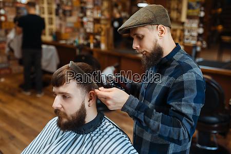 barbier haelt kamm und schneidet die