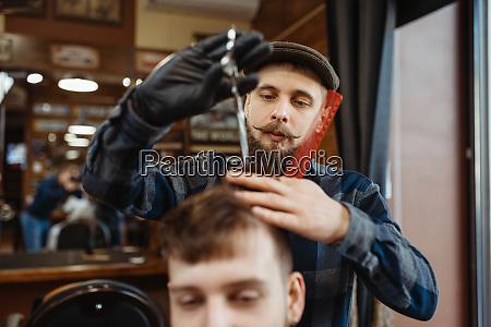 barbier macht stilvolle haarschnitt zu kunden