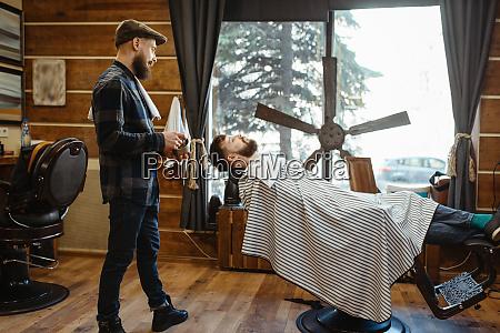 barbier in hut und baertigen kunden